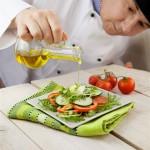Mise en scène d'une huile d'olive versée sur une salade de crudités